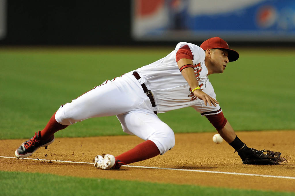 . PHOENIX, AZ - APRIL 25:  Martin Prado #14 of the Arizona Diamondbacks misses a ground ball against the Colorado Rockies at Chase Field on April 25, 2013 in Phoenix, Arizona.  (Photo by Norm Hall/Getty Images)