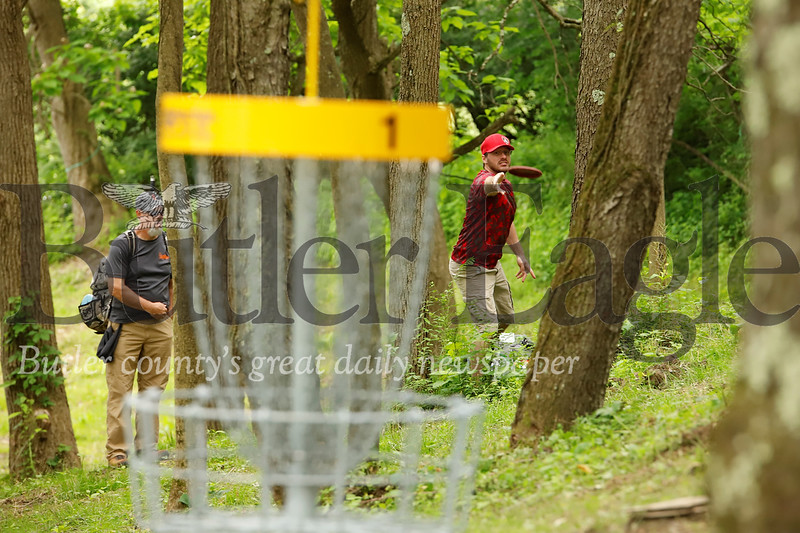Josh Simps tosses a disc towards the basket on hole one at the North Boundary Park disc golf course. Simps, his brother and friends were the first group to play through the course following Saturday's official grand opening ribbon cutting ceremony. Seb Foltz/ Butler Eagle