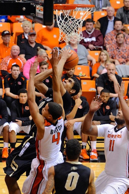 . Colorado\'s Josh Scott (40) shoots against Oregon State\'s Challe Barton (4) and Joe Burton (11) during the first half of an NCAA college basketball game in Corvallis, Ore., Sunday, Feb. 10, 2013. (AP Photo/Greg Wahl-Stephens)