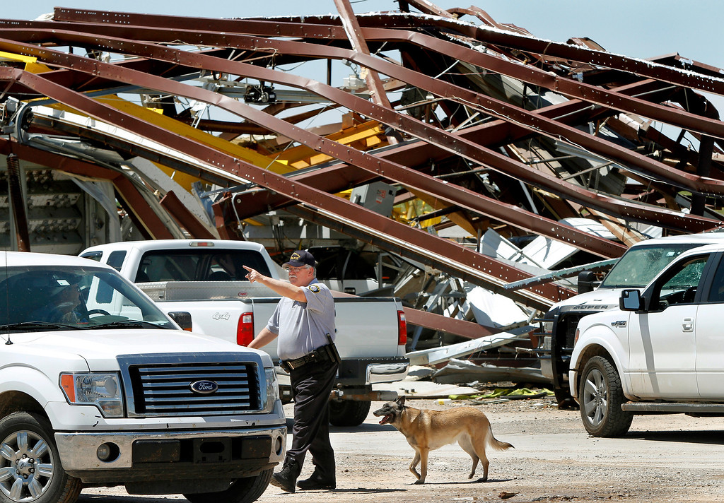 . A police officer offers directions to a driver leaving this heavily damaged supply yard for Cactus Drilling Company on State Highway 66 in El Reno, Okla. on Saturday, June 1, 2013. Employee David Stottemyre was working in the lot when the tornado took aim at the plant. Stottemyre ran inside the large supply storage building and took shelter as the tornado passed over, leaving the building in a twisted pile of steel and metal. He was not injured. (AP Photo/The Oklahoman, Jim Beckel)
