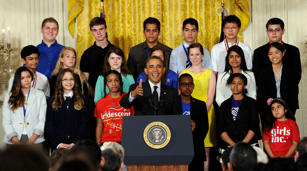 . President Barack Obama speaks with some of the 2014 White House Science Fair kids behind him, Tuesday, May 27, 2014, in the East Room of the White House in Washington.  (AP Photo/Susan Walsh)