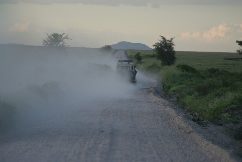 . A Land Cruiser throws up dust clouds as it speeds through Serengeti National Park, Tanzania, Africa.