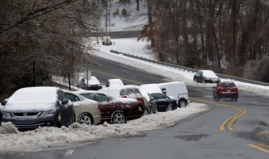 . Abandoned vehicles line a roadside following a snow and ice storm in Chapel Hill, N.C., Thursday, Feb. 13, 2014. The National Weather Service issued a winter storm warning lasting into Thursday covering 95 of the state\'s 100 counties. (AP Photo/Gerry Broome)