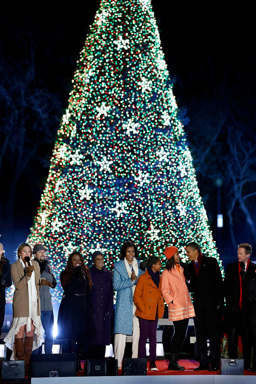 . President Barack Obama, second from right, first lady Michelle Obama, center, Sasha Obama, Malia Obama and Michelle Obama\'s mother Marian Robinson, left of center, and others participate in the 90th annual National Christmas Tree Lighting ceremony on the Ellipse south of the White House, Thursday, Dec. 6, 2012 in Washington. (AP Photo/Alex Brandon)