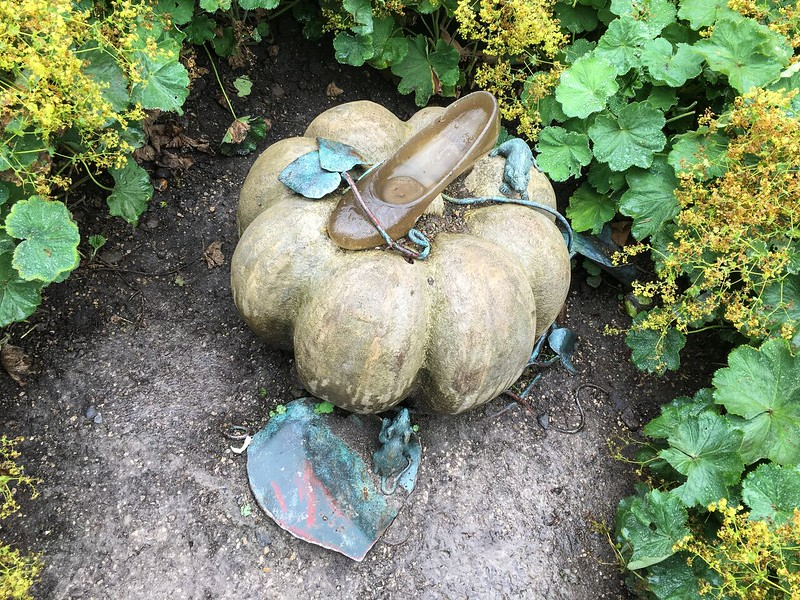 round stone in a garden with a shoe on top