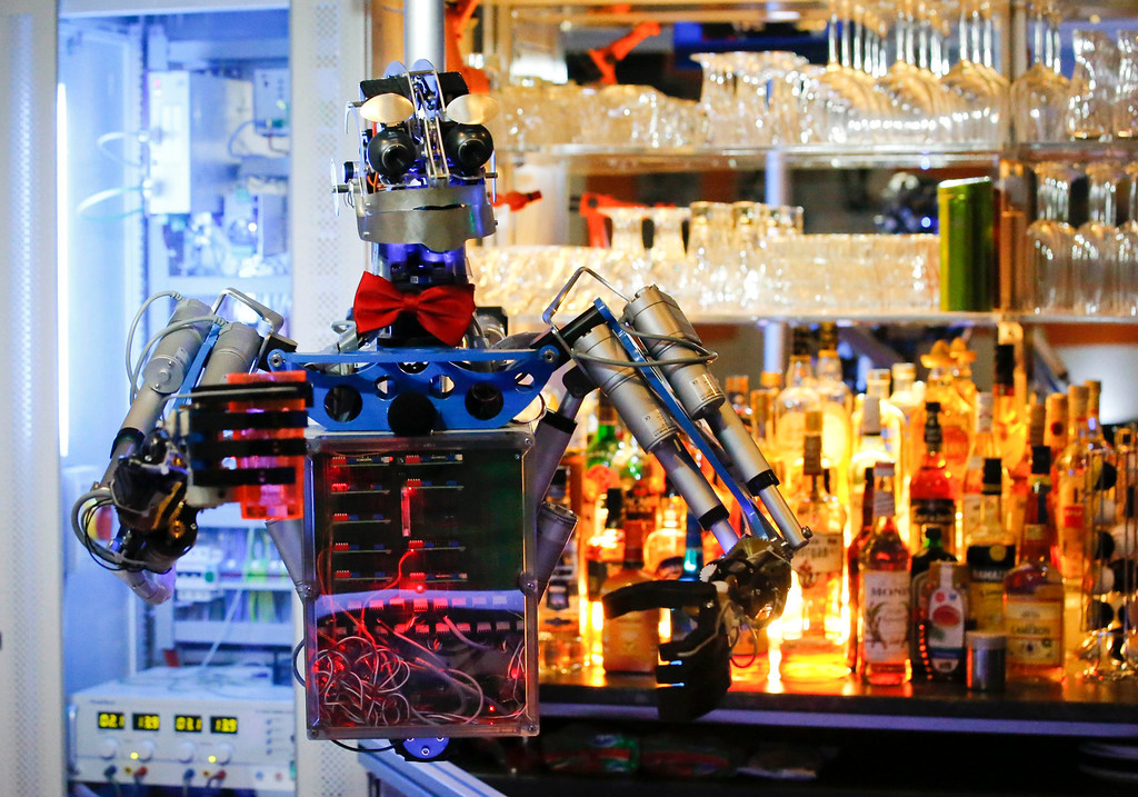 ". Humanoid robot bartender ""Carl\"" is on standby to prepare a drink for guests at the Robots Bar and Lounge in the eastern German town of Ilmenau, July 26, 2013. \""Carl\"", developed and built by mechatronics engineer Ben Schaefer who runs a company for humanoid robots, prepares spirits for the mixing of cocktails and is able to interact with customers in small conversations. Picture taken July 26, 2013. REUTERS/Fabrizio Bensch"