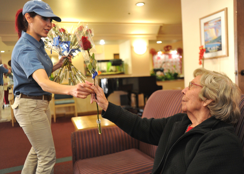 . Tamara Torres, with Honda, Gives resident, Isabel Fruta, a receive long-stem red rose on Valentine\'s Day at Merill Gardens in Whittier on Thursday February 14, 2013.  The Helpful Guys in Blue, a group sponsored by the Southern California Honda Dealers Association surprise Whittier residents with a complimentary red roses. (SGVN/Staff Photo by Keith Durflinger)