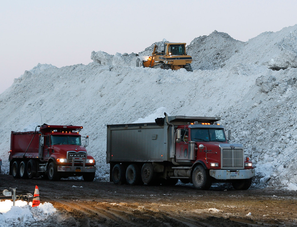 . Dump trucks wait to unload snow at the Central Terminal that was removed from south Buffalo neighborhoods after heavy lake-effect snowstorms on Friday, Nov. 21, 2014, in Buffalo, N.Y. A snowfall that brought huge drifts and closed roads in the Buffalo area finally ended Friday, yet residents still couldn\'t breathe easy, as the looming threat of rain and higher temperatures through the weekend and beyond raised the possibility of floods and more roofs collapsing under the heavy loads.  (AP Photo/Mike Groll)