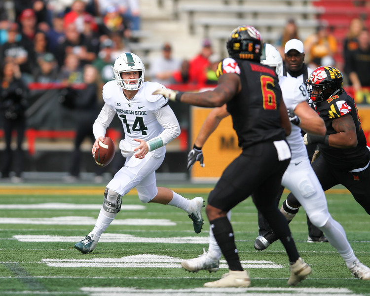 Michigan State quarterback #14 Brian Lewerke scrambles under pressure