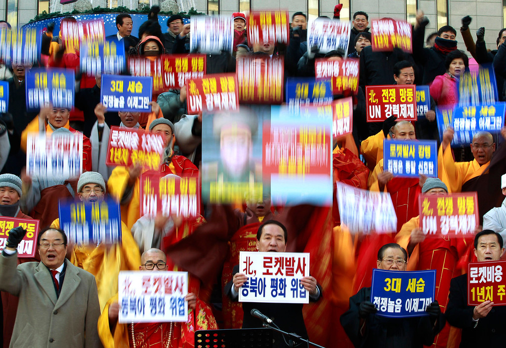 ". South Korean religious leaders raise placards and shout slogans during a rally denouncing North Korea\'s rocket launch in Seoul, South Korea, Wednesday, Dec. 12, 2012. North Korea fired a long-range rocket Wednesday in its second launch under its new leader, South Korean officials said, defying warnings from the U.N. and Washington only days before South Korean presidential elections. The words read ""Denounce North Korea\'s rocket launch and overthrow family succession through three generations!\"" (AP Photo/Ahn Young-joon)"
