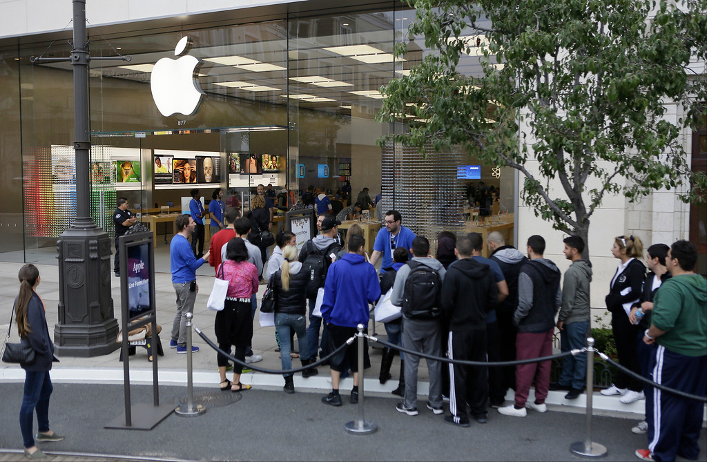 . Customers wait in line to buy the latest versions of the iPhone during the opening day of sales of the iPhone 5s and iPhone 5C at the Apple store at the Americana at Brand mall in Glendale, Calif., Friday, Sept. 20, 2013. (AP Photo/Damian Dovarganes)