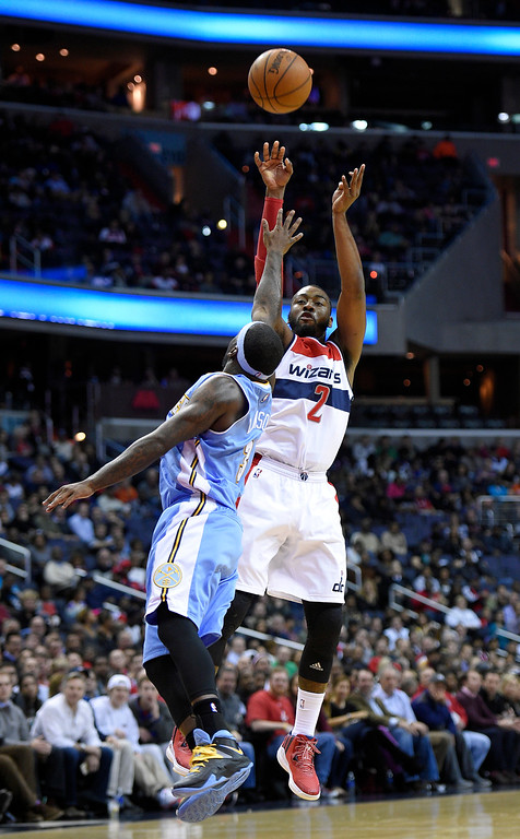 . Washington Wizards guard John Wall (2) shoots against Denver Nuggets guard Ty Lawson, left, during the second half of an NBA basketball game, Friday, Dec. 5, 2014, in Washington. (AP Photo/Nick Wass)