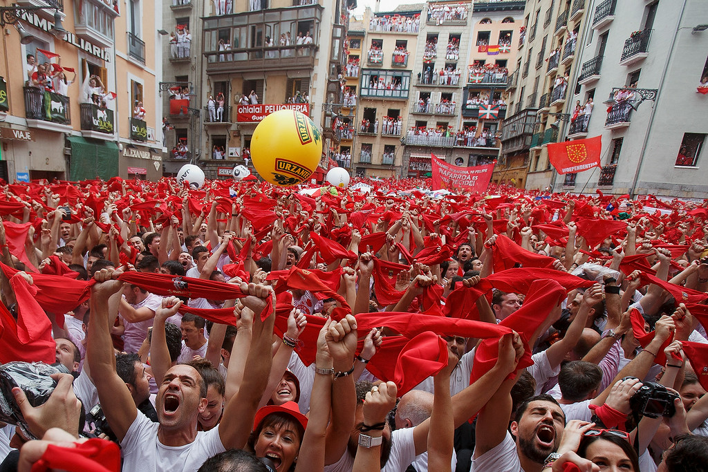 . Revellers hold up their red handkerchiefs during the opening and the firing of the \'Chupinazo\' rocket which starts the 2014 Festival of the San Fermin Running of the Bulls on July 6, 2014 in Pamplona, Spain. The annual Fiesta de San Fermin, made famous by the 1926 novel of US writer Ernest Hemmingway entitled \'The Sun Also Rises\', involves the daily running of the bulls through the historic heart of Pamplona to the bull ring.  (Photo by Pablo Blazquez Dominguez/Getty Images)