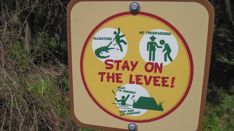 Warning sign with cartoon drawings of mud, alligators, police