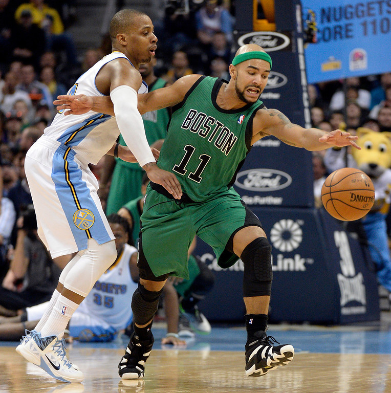 . Boston Celtics point guard Jerryd Bayless (11) reaches out for the ball after getting fouled by Denver Nuggets shooting guard Randy Foye (4) during the fourth quarter January 7, 2014 at Pepsi Center. (Photo by John Leyba/The Denver Post)