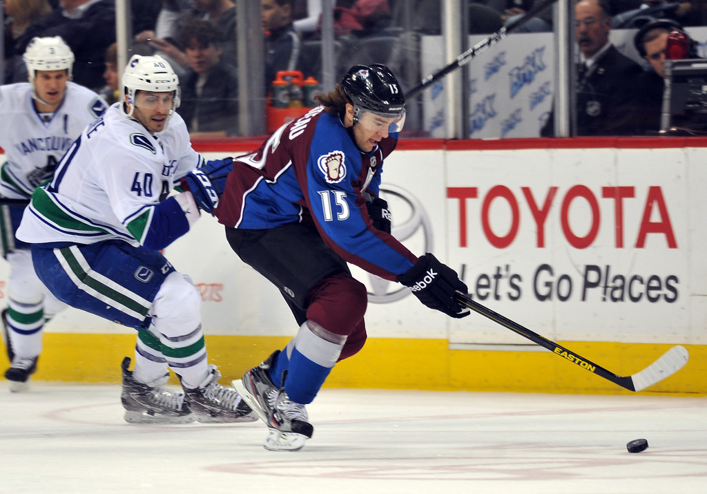 . DENVER, CO. - APRIL 13 : PA Parenteau of Colorado Avalanche (15) controls the puck aginst Maxim Lapierre of Vancouver Canucks (4) in the 1st period of the game at Pepsi Center. Denver, Colorado. April 13, 2013. Colorado won 4-3. (Photo By Hyoung Chang/The Denver Post)
