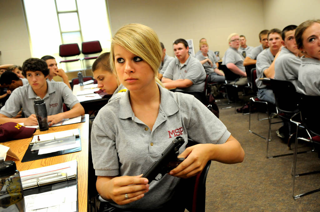 ". Macy Hennen, 16, from Pierz, Minn., listens to a Minnesota State Patrol sergeant talk about different kinds of guns during a Minnesota State Patrol High School Summer Camp at Camp Ripley, near Little Falls. The sergeant had the cadets pass around the unloaded guns. Hennen said she is ""here for the experience. To see if I\'m interested.\"" (Pioneer Press: Jean Pieri)"