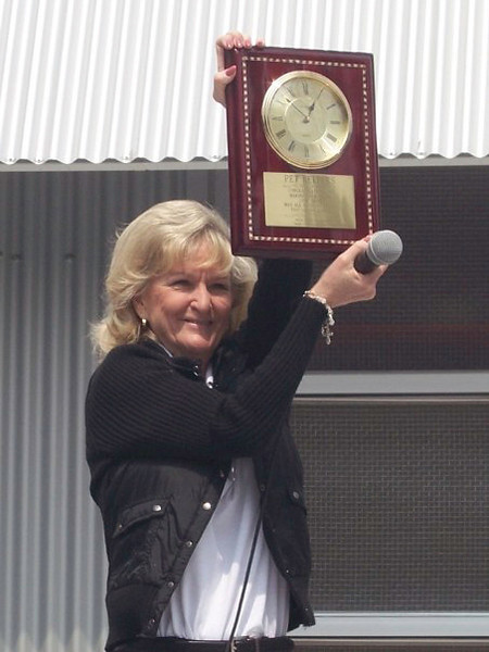 Carol Linville holding up the clock plaque from her family on Pet Helpers Grand Opening Day at 1447