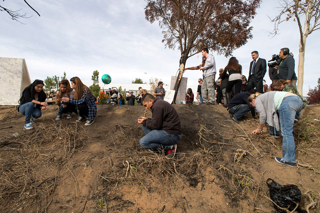 . People look for pieces of car at a memorial for actor Paul Walker who was killed on Saturday, November 30, 2013 in Valencia, Ca. Walker was a passenger in a 2005 Porsche Carrera GT, believed to be driven by his friend Roger Rodas, that crashed and burst in to flames. (Photo by Hans Gutknecht/Los Angeles Daily News)