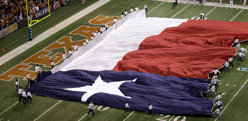 . The Texas flag is run on to the field prior to the Alamo Bowl NCAA football game between Oregon State and Texas, Saturday, Dec. 29, 2012, in San Antonio.  (AP Photo/Eric Gay)