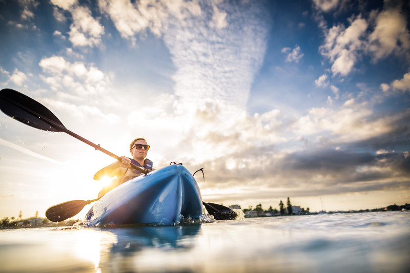 Girl in a blue canoe at sunset
