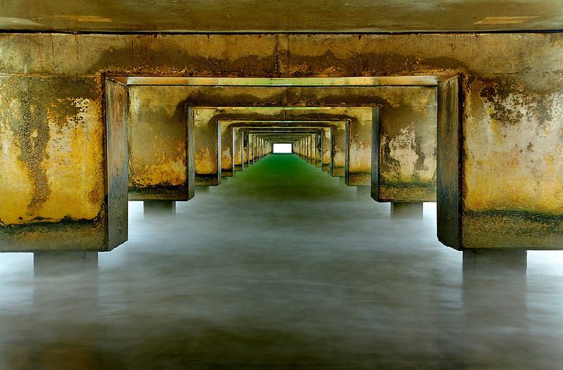 I wanted to create a surreal image that showed the interesting colors and detail under the Hanalei pier. A long exposure softened the waves which occasionally brushed up against the top part of the concrete in this image. I had to abort my 30 second planned exposure several times and run away from larger waves, until I had a good long period of smaller waves.  I like the symmetry underneath piers, so I always try to capture it if I can.