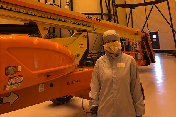 Marissa Johnsey Stewart wears clean room garments (aka: a bunny suit) in one of the Kennedy Space Center facilities, next to a payload fairing.