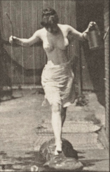 Semi-nude woman crossing brook on stepping-stones with a fishing pole and can
