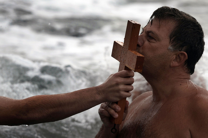 . A faithful kisses a wooden cross after retrieving it from the sea during a ceremony of the blessing of the waters marking the orthodox Epiphany Day in the southern suburb of Athens on January 6, 2014. ARIS MESSINIS/AFP/Getty Images