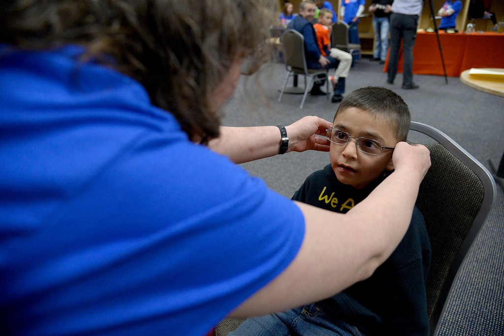 . Eileen Viapando fits Daniel  Guerroro , 7, with a new pair of prescription glasses on Monday, April 14, 2014.  (Photo by John Leyba/The Denver Post)