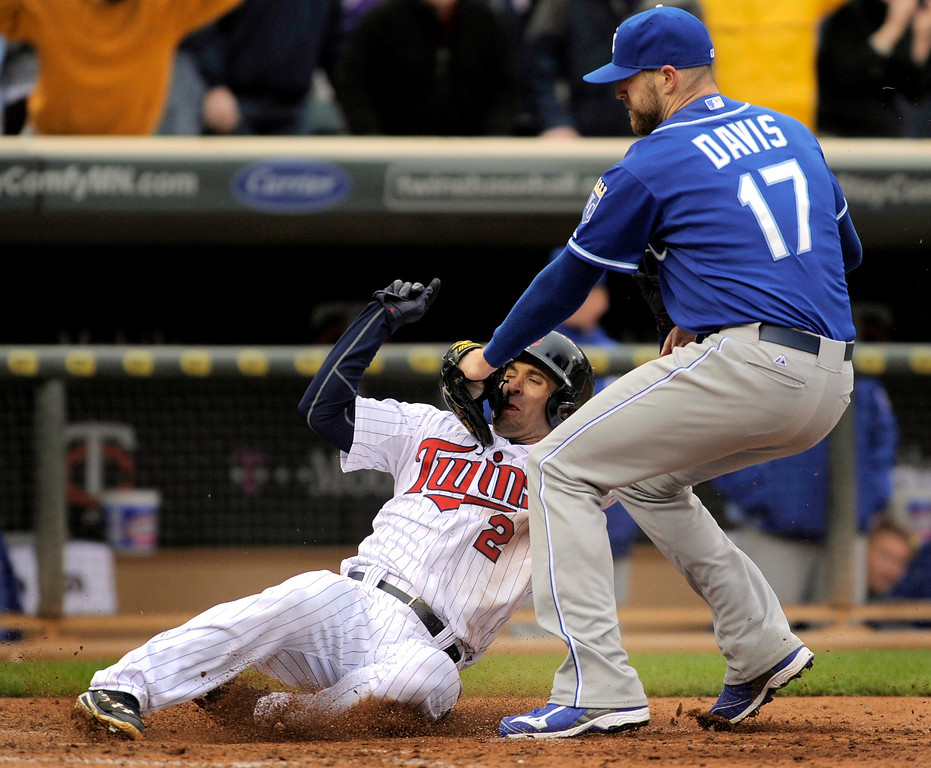 . Kansas City Royals pitcher Wade Davis (17) puts a late tag on the Minnesota Twins Brian Dozier, who scored with the go-ahead run during the ninth inning of a baseball game in Minneapolis, Sunday, April 13, 2014. Minnesota won 4-3. (AP Photo/Tom Olmscheid)