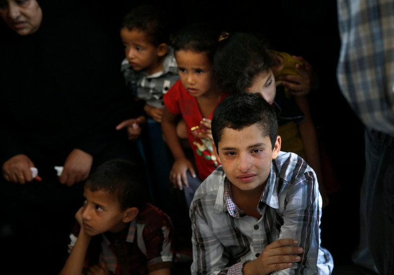 . Palestinian children wait for the bodies of Sarah Omar el-Eid, 4, her father Omar, 26, and her uncle Jihad, 27, to be brought in a house  during their funeral in Rafah, southern Gaza Strip, Tuesday, July 15, 2014. The three were killed by an Israeli strike late Monday. An Egyptian truce proposal for the conflict in Gaza quickly unraveled Tuesday, after the Islamic militant group Hamas rejected the plan.(AP Photo/Lefteris Pitarakis)