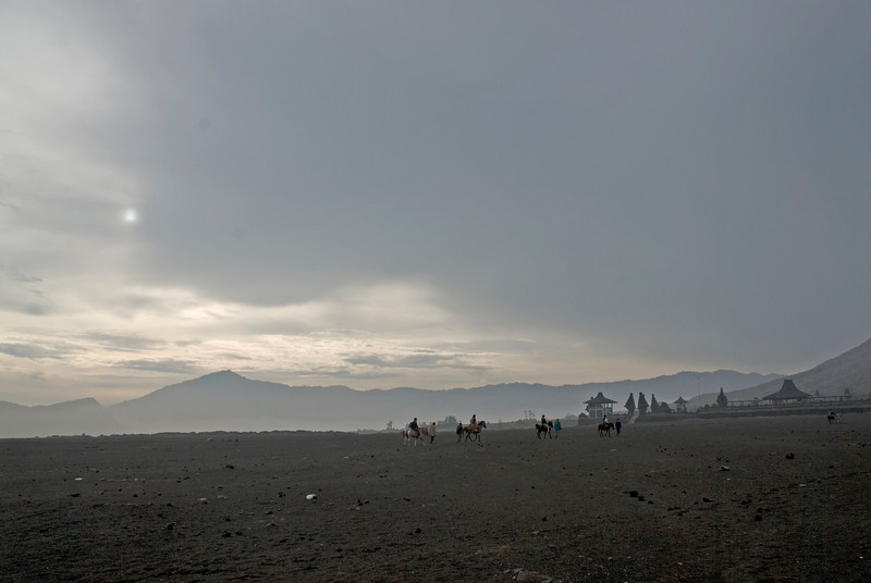 People riding horses in haze near Mount Bromo in Indonesia
