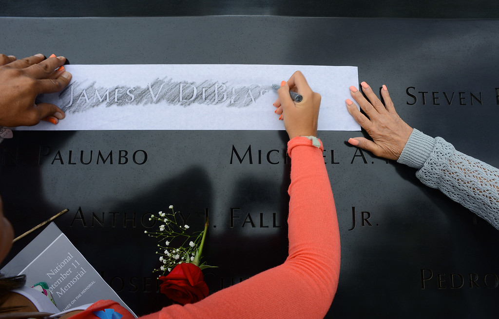 . Anthony DeBlase,  left, and his mother Anita, right, hold the paper as Alexandra DeBlase rubs the name of their lost loved one James V DeBlase during memorial observances on the 13th anniversary of the Sept. 11 terror attacks on the World Trade Center in New York, Thursday, Sept. 11, 2014.   (AP Photo/The Daily News, Robert Sabo, Pool)