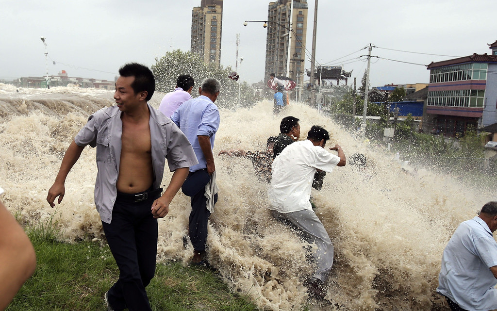 """. This picture taken on August 22, 2013 shows onlookers being washed away from huge waves from the \""""Haining tide\"""" - a daily occurrence when the river tides hit the banks of the city - as the waves surged higher than usual due to the influence of Typhoon Trami in the region in Haining, in eastern China\'s Zhejiang province. State media reported on August 23 that 30 people were injured and 11 still in hospital after the wave hit.  Typhoon Trami, the 12th typhoon to hit China this year, brought rainstorms and wreaked havoc in eastern China after landing in Fujian Province early on August 22.   AFP PHOTOSTR/AFP/Getty Images"""
