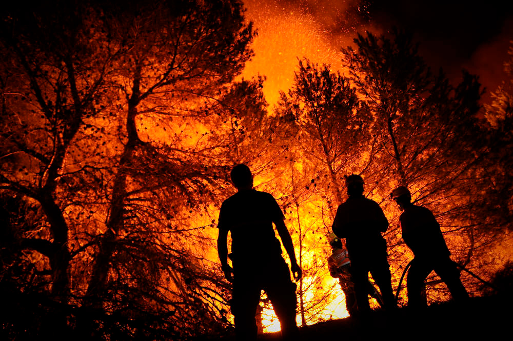 . Firefighters of Alcoy and Elda try to extinguish a fire in Torre de Macanes near Alicante, on August 13, 2012. One person was killed and three injured Sunday as firefighters battled wildfires across Spain, authorities said, the latest victims in a sweltering summer of forest blazes. AFP PHOTO/Pedro  ARMESTRE/AFP/Getty Images
