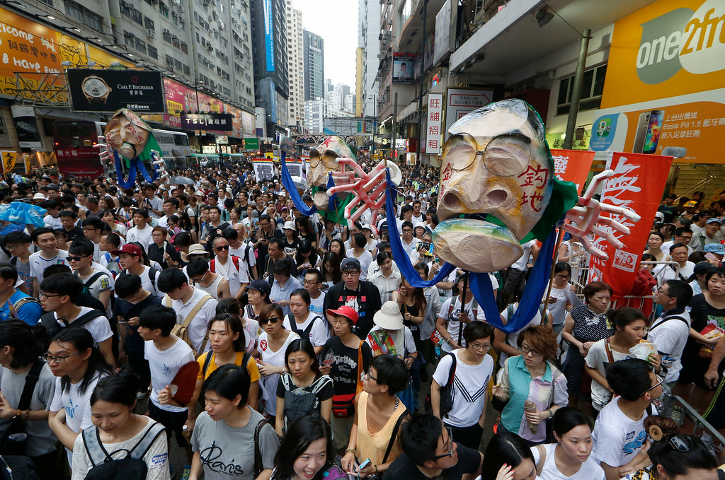 . Protesters hold an effigy of Hong Kong Chief Executive Leung Chun-ying as they march during an annual protest in downtown Hong Kong Tuesday, July 1, 2014. Hong Kong residents marched through the streets of the former British colony to push for greater democracy in a rally fueled by anger over Beijing\'s recent warning that it holds the ultimate authority over the southern Chinese financial center. The protest comes days after nearly 800,000 residents voted in a mock referendum aimed at bolstering support for full democracy. (AP Photo/Kin Cheung)