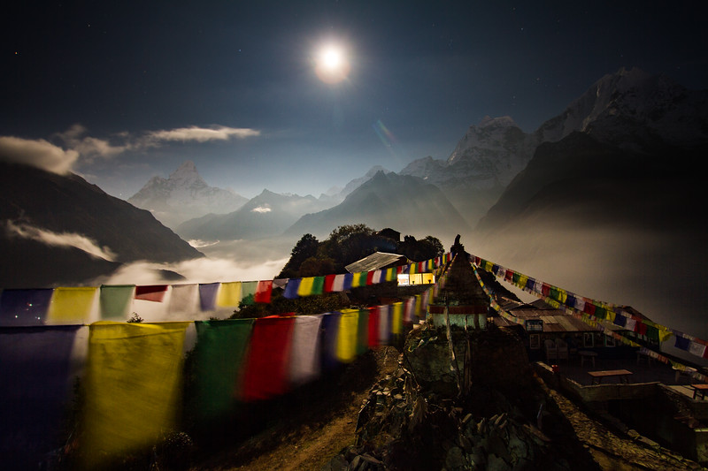 The full moon is seen rising over Nepal's Himalaya mountains while a Buddhist stupa in the village of Mongla graces the foreground