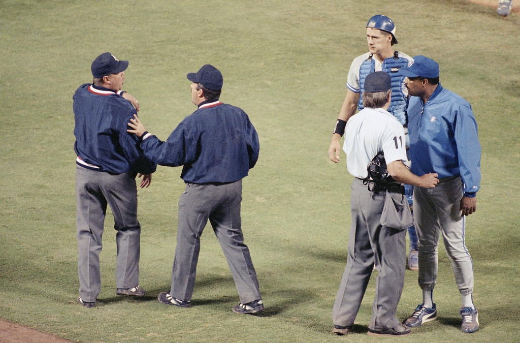 . Home plate umpire Don Denkinger (11) keeps Toronto Blue Jays manager Cito Gaston in place as Tim Tschida, middle, steers fellow umpire Jim Joyce away following a bench clearing brawl with the California Angels in the sixth inning at Anaheim Stadium, Wednesday, June 3, 1993, Anaheim, Calif. Jays catcher Pat Borders, watches. The Jays beat the Angels 7-6. (AP Photo/Douglas C. Pizac)