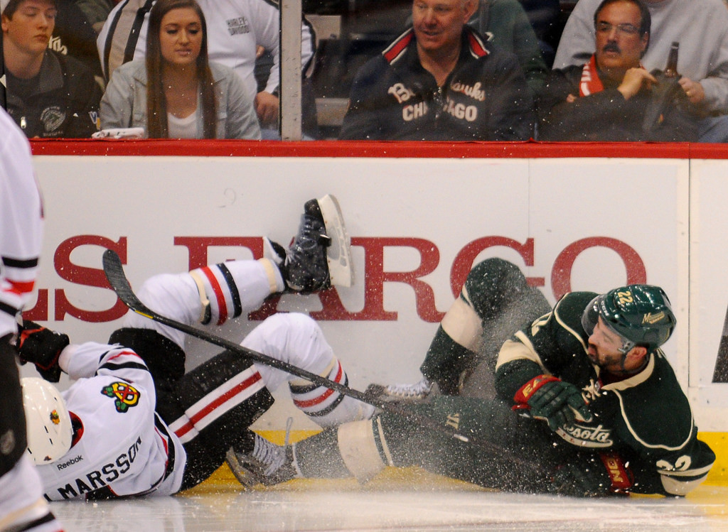 . Minnesota right wing Cal Clutterbuck, right, is pummeled by Chicago defenseman Niklas Hjalmarsson during the overtime period. (Pioneer Press: John Autey)