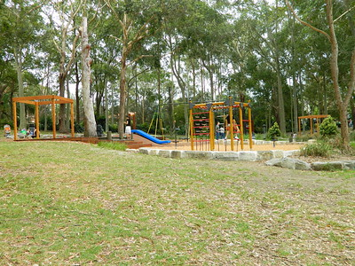 open plan timber cubby and blue plastic slide on mound and climbing frame with rope net