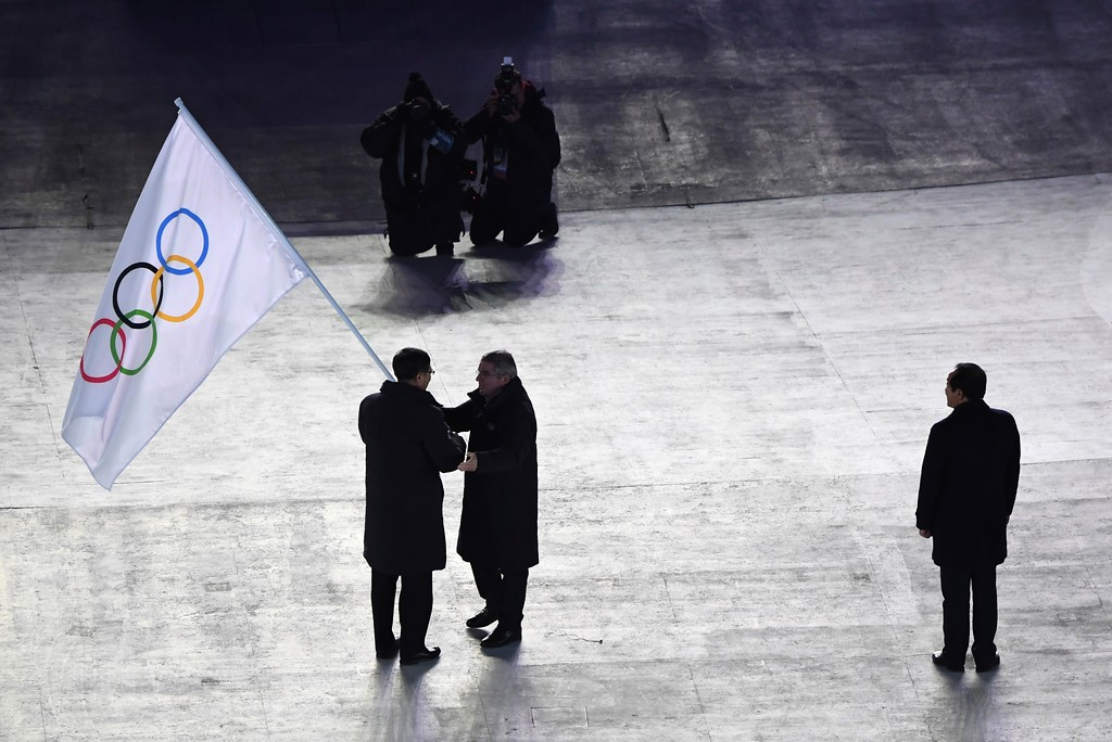 . International Olympic Committee President Thomas Bach, center, hands the Olympic flag to the mayor of Beijing, China, Chen Jining, during the closing ceremony of the 2018 Winter Olympics in Pyeongchang, South Korea, Sunday, Feb. 25, 2018. Sim Jae-guk, the mayor of Pyeongchang, South Korea, is at right. (Florien Choblet/Pool Photo via AP)