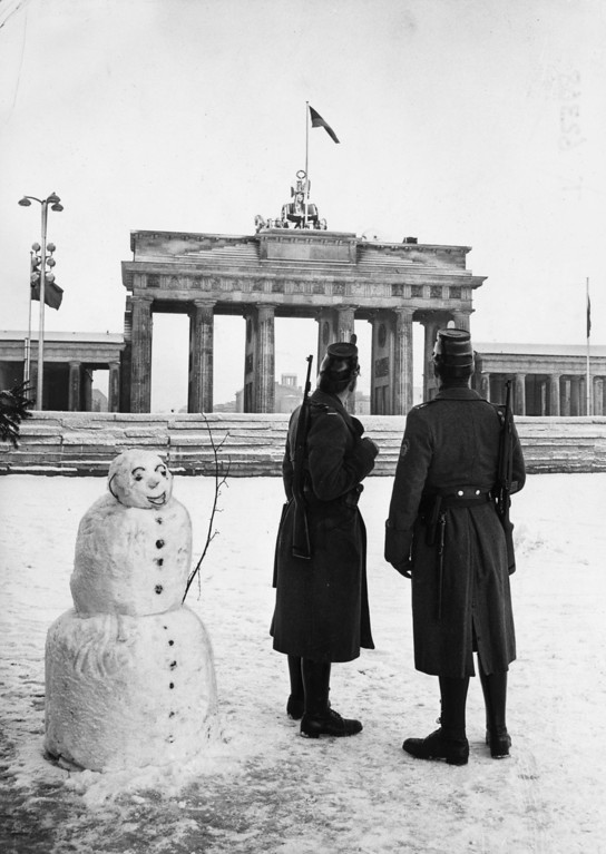 . Two West Berlin policemen with their new American rapid fire rifles on duty with a snowman on Christmas Day in front of the Berlin Wall at the Brandenburg Gate, December 25, 1961.  (Photo by Keystone/Getty Images)