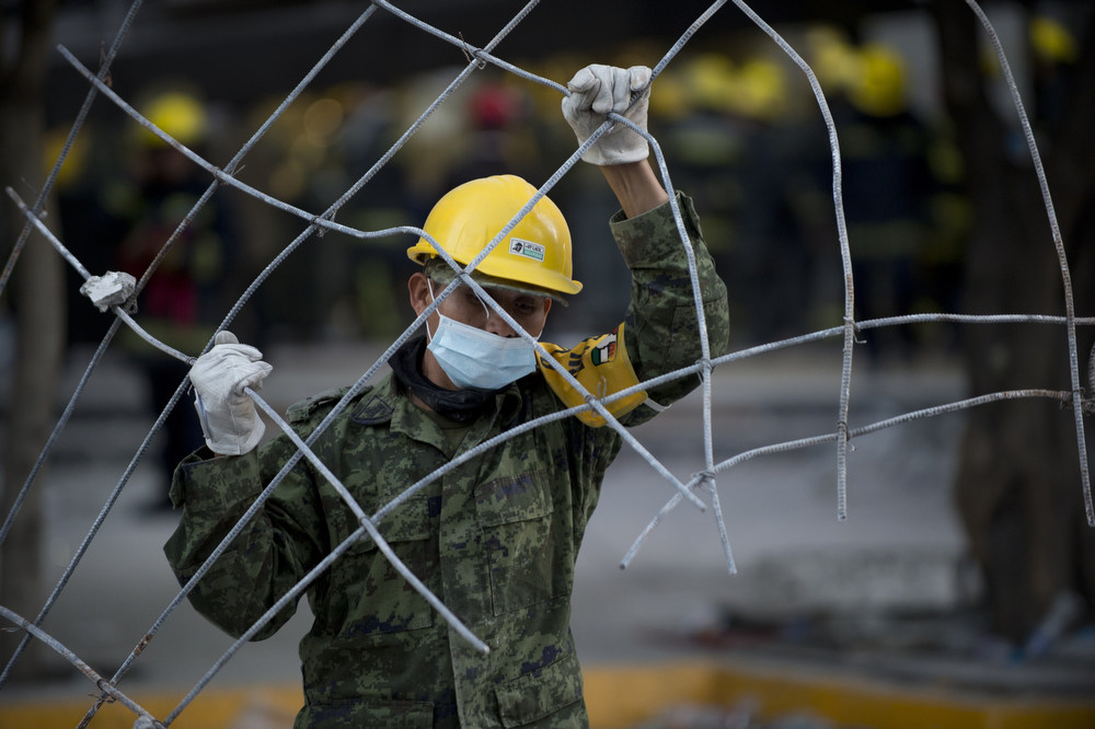 Description of . A Mexican soldier removes debris from the headquarters of the state-owned Mexican oil giant Pemex in Mexico City on February 1, 2013, following a blast inside the building. An explosion rocked the skyscraper, leaving up to now 25 dead and 100 injured, as a plume of black smoke billowed from the 54-floor tower, according to official sources.  AFP PHOTO/ YURI  CORTEZ/AFP/Getty Images