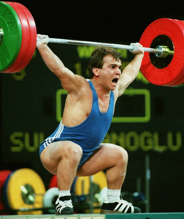 """. FILE- In this July 22, 1996 file photo, Naim Suleymanoglu, of Turkey, lifts 147.5kg, at the Summer Olympics in Atlanta. Turkey\'s official news agency said Saturday, Nov. 18, 2017, Suleymanoglu, the Turkish weightlifter who was known as \""""Pocket Hercules\"""" and who won three straight Olympic gold medals for Turkey between 1988 and 1996, has died. Suleymanoglu was considered one of the sport\'s greatest athletes and earned his nickname for his strength and diminutive size. He was 50. (AP Photo/Michael Probst, File)"""