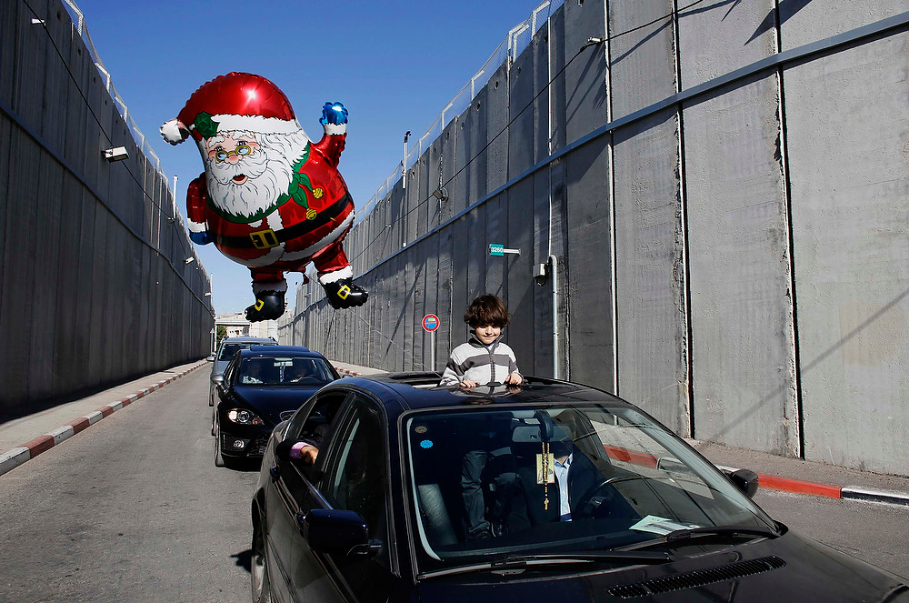 . A boy holds a santa claus balloon as a convey of cars transporting the Latin Patriarch of Jerusalem Fouad Twal cross through an Israeli checkpoint into the West Bank city of Bethlehem on December 24, 2012. Twal crossed from Jerusalem into Bethlehem on Monday to attend a procession outside the Church of the Nativity, the site revered as the birthplace of Jesus. REUTERS/Ammar Awad