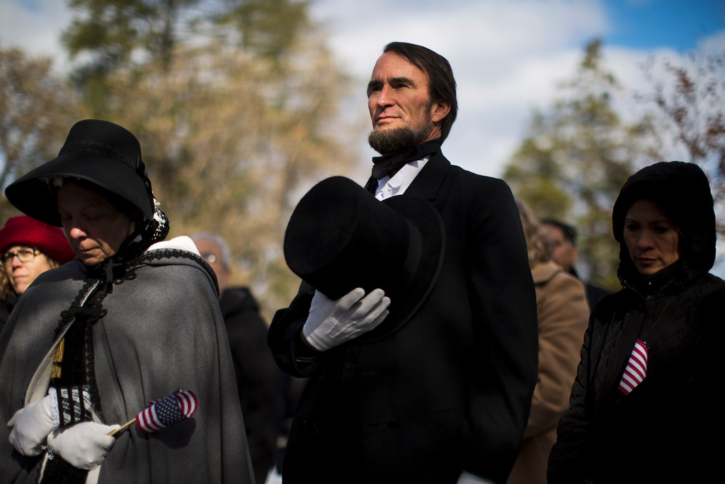. John Voehl portraying President Abraham Lincoln,  covers his hart during a ceremony commemorating the 150th anniversary of the dedication of the Soldiers\' National Cemetery and President Abraham Lincoln\'s Gettysburg Address, Tuesday, Nov. 19, 2013, in Gettysburg, Pa.  (AP Photo/Matt Rourke)