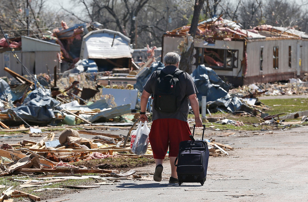 . Robert Swanson carts out some of his belongings through a tornado-damaged mobile home park in Sand Springs, Okla., Thursday, March 26, 2015. (AP Photo/Sue Ogrocki)