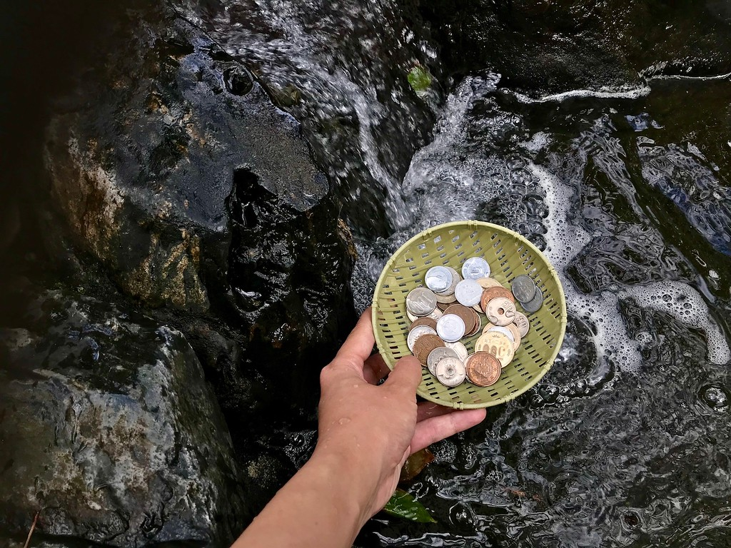 Washing coins in the water.