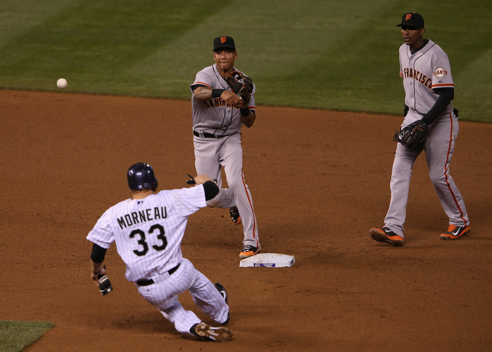 . Shortstop Ehire Adrianza #53 of the San Francisco Giants turns a double play on Justin Morneau #33 of the Colorado Rockies as second baseman Joaquin Arias #13 of the San Francisco Giants follows the play in the fourth inning at Coors Field on April 22, 2014 in Denver, Colorado.  (Photo by Doug Pensinger/Getty Images)